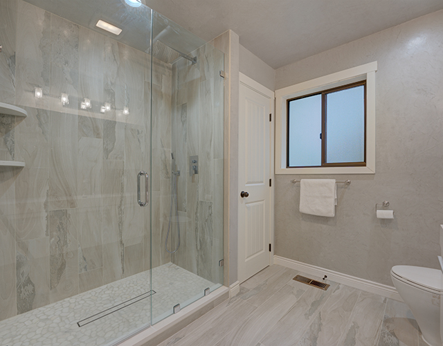 Modern white and grey bathroom with walk in glass shower finished by LCM
